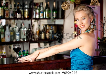 Young beautiful blonde woman  in a stylish outfit with a glass of wine standing at a bar counter