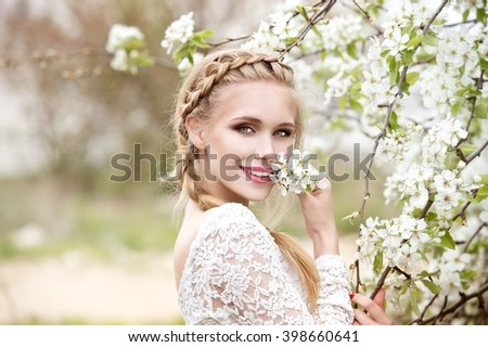 Young beautiful blonde woman in blooming garden. Bride.