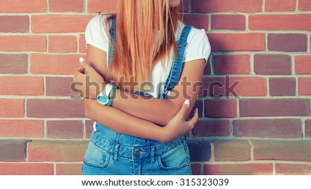 Young beautiful blonde woman in boiler suit (jeans overalls) on red brick wall background. Hipster girl no face shot,  a lot of space for text - stock photo