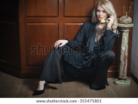 Young beautiful blonde woman in elegant black suit talking by phone sitting relaxed on the floor. Seductive fair hair girl leaning on wooden cabinet holding a vintage phone in classic interior - stock photo