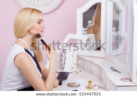 Young beautiful blonde woman is getting ready and doing makeup in front of mirror for dating on valentine day.