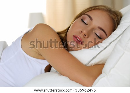 Young beautiful blonde woman portrait lying in bed sleeping at home late in the morning after hard working day tired. Sweet dreams, good morning, new day, weekend, day off, holidays concept - stock photo
