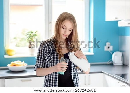 Young beautiful blonde woman pouring a milk in kitchen. Standing in front of a window in the bright kitchen - stock photo
