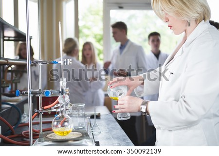 Young beautiful blonde woman researcher chemist preparing substances for chemical use with laboratory dishes.Pharmacist making chemical apparatus.Mixing a medicine in university pharmacy laboratory - stock photo