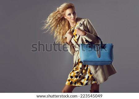 Young beautiful blonde woman wearing fashionable autumn coat and blue handbag - stock photo