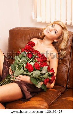 Young beautiful blonde woman with bunch of red roses - stock photo