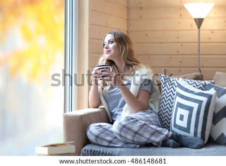 Young beautiful blonde woman with cup of coffee sitting home by the window. Autumn fall trees reflection on the glass. Lazy day off concept
