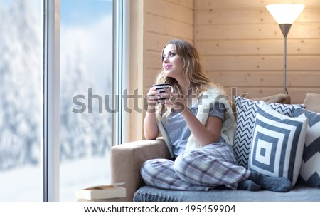 Young beautiful blonde woman with cup of coffee sitting home in living room by the window. Winter snow landscape view. Lazy day off concept