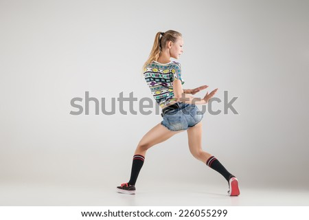 young beautiful booty dancer posing on studio background - stock photo