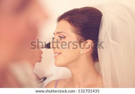 Young beautiful bride applying wedding make-up - stock photo