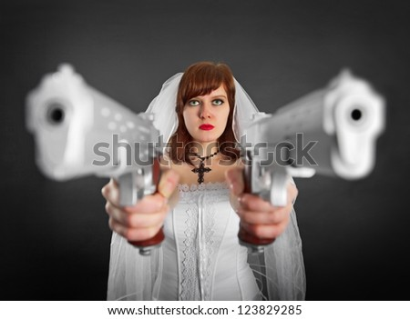 Young beautiful bride armed with two jumbo pistols - stock photo