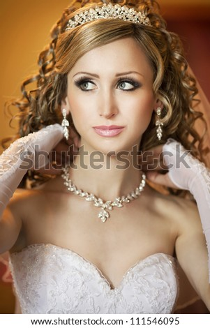 young beautiful bride at home waiting for groom. slim woman in luxury wedding dress in diamond jewelry and tiara posing. Sexy smiling bride with wedding makeup looks happy.series. autumn - stock photo