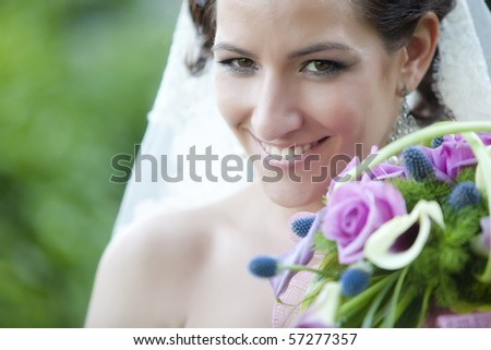Young beautiful bride close portrait with bouquet - stock photo