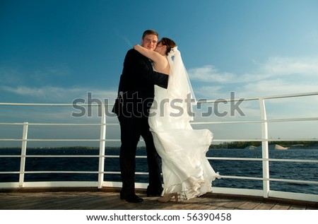 Young beautiful bride embracing each other on the deck near the river - stock photo