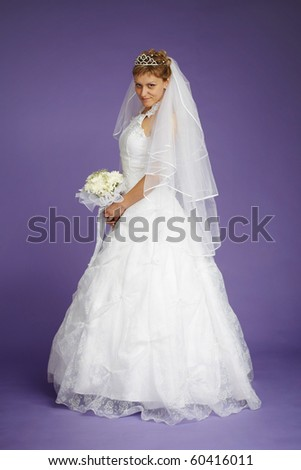 Young beautiful bride in a white dress on a purple background - stock photo