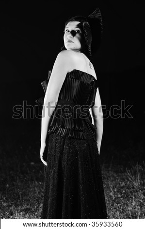young beautiful bride in black wedding dress in dar at night