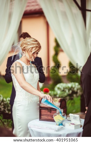 young beautiful bride pours sand with vase - stock photo