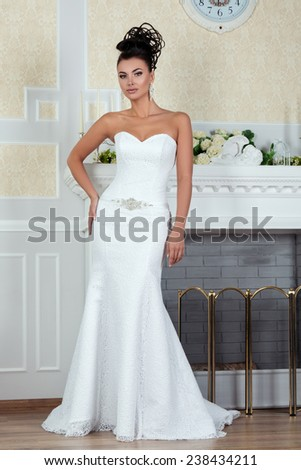 Young beautiful bride standing in luxurious wedding dress near fireplace - stock photo
