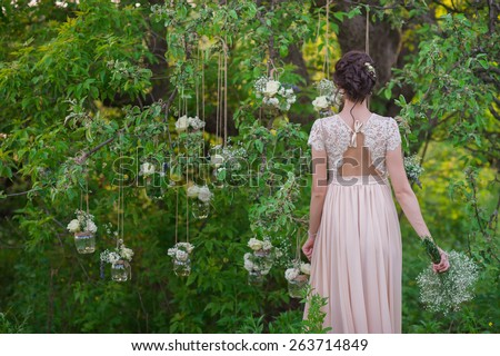 Young beautiful bride standing with his back amid banks decorated with roses tree,decor,concept,wedding decorations - stock photo