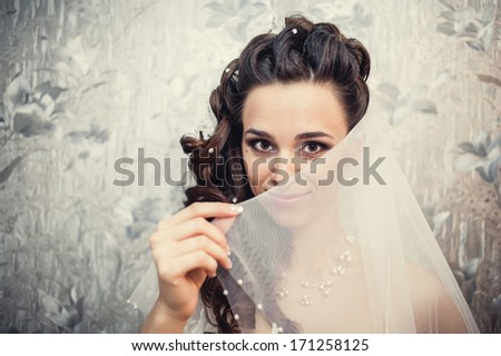 Young beautiful bride waits for groom and plays her veil. Gorgeous bride in wedding dress in luxury interior posing. Romantic rich happy girl in bridal dress smiling have final preparation for wedding