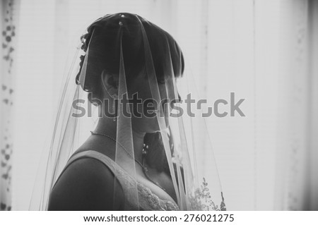 Young beautiful bride waits for groom near the window. Beautiful Bride lit by sunlight from a window. beautiful young bride standing beside a large window waiting - stock photo