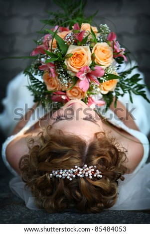 Young beautiful bride with red hair and flowers - stock photo