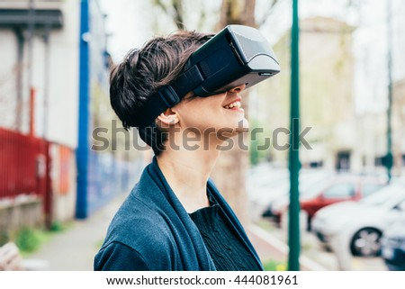 Young beautiful brown short hair caucasian woman using 3D viewer looking up - futuristic, multitasking, technology concept - stock photo