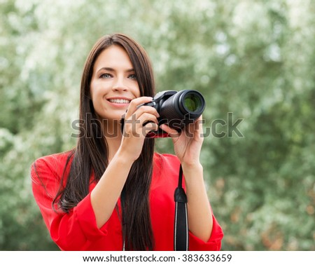Young beautiful brunette being happy with new slr photo camera.