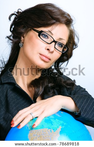 Young beautiful brunette businesswoman holding the globe - stock photo