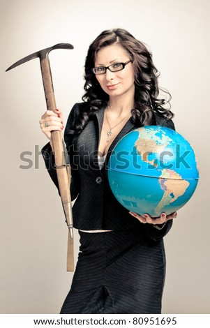 Young beautiful brunette businesswoman holding the globe and pick - stock photo