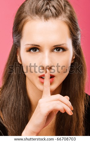 Young beautiful brunette calls for silence, having brought to mouth index ????, on red background.