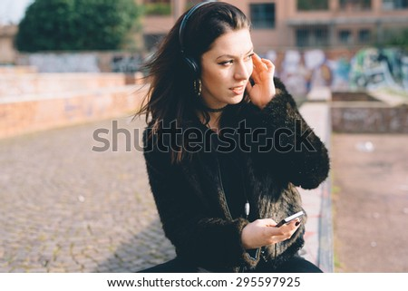Young beautiful brunette caucasian girl listening to the music with headphones in the city - music, relax, serenity concept - stock photo