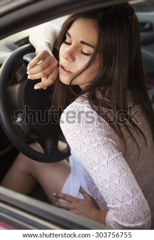 Young beautiful brunette caucasian woman  driving a red car. summer day, outdoors