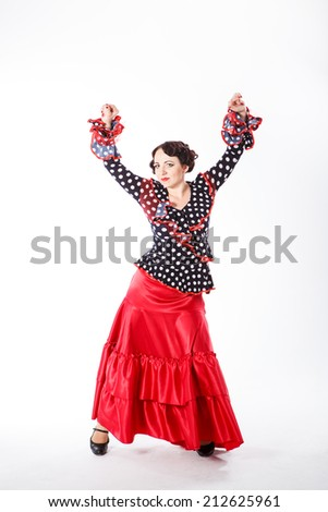 young beautiful brunette female spanish flamenco dancer in black shirt and red flamenco skirt dancing with her arms in studio on gray background - stock photo