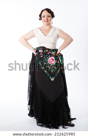 young beautiful brunette female spanish flamenco dancer in white blouse and black flamenco skirt posing with black flower shawl in her arms in studio on gray background - stock photo