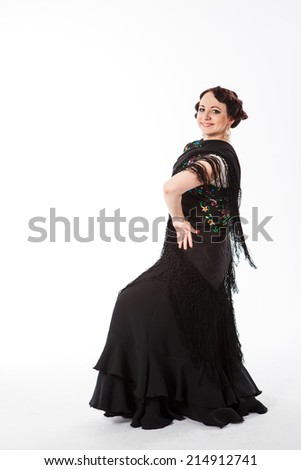 young beautiful brunette female spanish flamenco dancer in white shirt and black flamenco skirt posing with black flower shawl in her arms in studio on gray background - stock photo