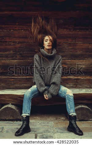 young beautiful brunette girl in a warm knitted sweater in jeans and boots posing on the street, on the street porttrait, to close the model - stock photo