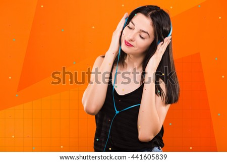 Young beautiful brunette girl, in black blouse, listening to music with big blue headphones on geometric orange background with blue and white dots - stock photo