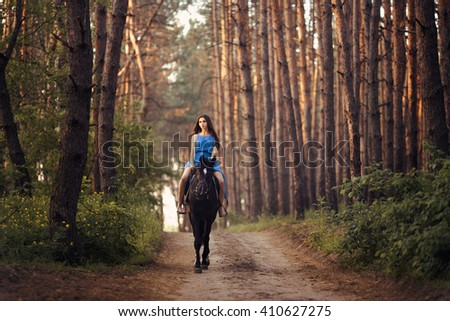 Young beautiful brunette girl in blue dress ride on the black horse in forest - stock photo