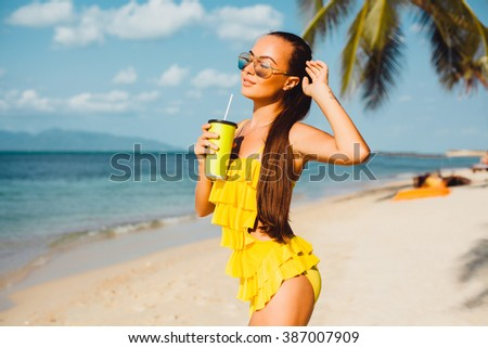 young beautiful brunette girl in sunglasses and yellow bikini tanned skin, posing on the beach, drinking fresh morning smoothies, fruit juice,cocktail fashion outdoor, close up, cute,pretty woman - stock photo