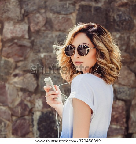 young beautiful brunette girl in sunglasses listen the music in your smartphone, smiling good humor, hipster style posing on street, outdoor portrait, close up - stock photo