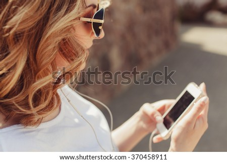 young beautiful brunette girl in sunglasses listen the music in your smartphone,smiling good humor,hipster style posing on street,outdoor portrait, close up,photos in instagram social network facebook - stock photo
