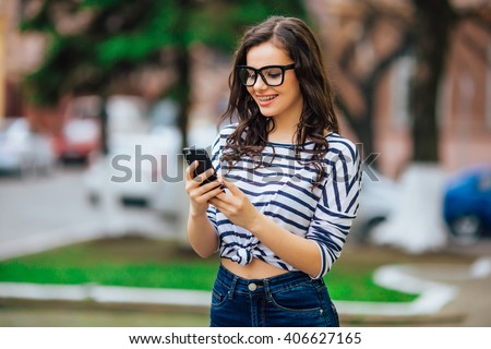young beautiful brunette girl in sunglasses listen the music in your smartphone,smiling good humor,hipster style posing on street,outdoor portrait, close up - stock photo