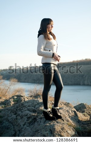 Young beautiful brunette girl posing in the autumn background