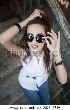 young beautiful brunette girl sitting on the steps of hipster glasses ?uropeans woman fashion sunglasses young beautiful joy
