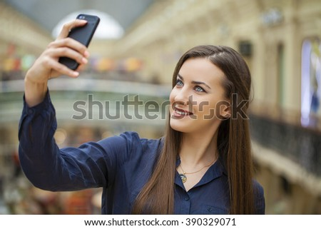 Young beautiful brunette girl taking selfie with mobile phone, in shop - stock photo