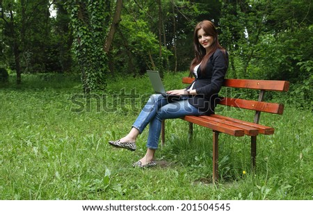 Young beautiful brunette girl using a notebook, sitting on a bench in the park