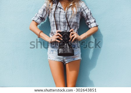 young beautiful brunette girl with a beautiful face and figure, hipster, retro posing with a camera on the outside, making photos, taking pictures, woman, photographer,vintage camera, outdoor portrait - stock photo