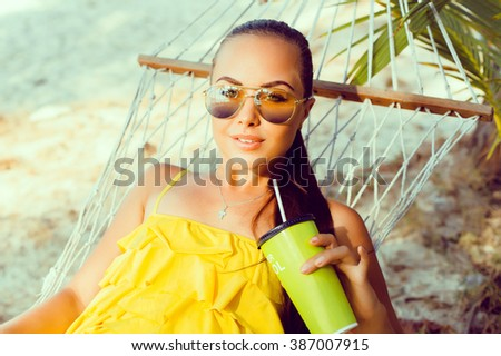 young beautiful brunette girl with a nice tan, drink smoothies in a hammock of glass, beautiful woman, healthy food, fresh fruit juice,outdoor portrait, close up - stock photo