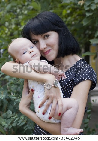 Young beautiful brunette holds on hands of baby - stock photo